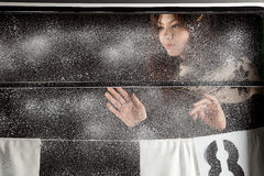 Young happy girl behind snow window on black background Royalty Free Stock Photography