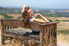 Young  happy girl on a bench Royalty Free Stock Images