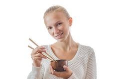 A young happy girl with bowl and chopsticks. Young smilling happy girl with bowl and chopsticks isolated on white Royalty Free Stock Photos