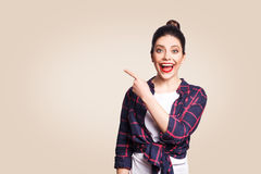 Young happy girl with casual style and bun hair pointing her finger sideways, demonstrating something on beige blank wall Royalty Free Stock Photo
