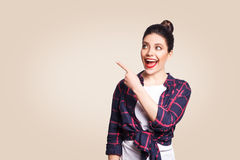Young happy girl with casual style and bun hair pointing her finger sideways, demonstrating something on beige blank wall Royalty Free Stock Photography