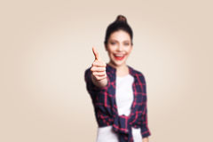 Young happy girl with casual style and bun hair thumbs up her finger, on beige blank wall with copy space looking at camera Stock Photos