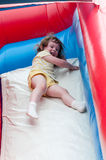 Young happy girl child riding inflatable slide outdoors on a warm summer day. Royalty Free Stock Image