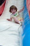 Young happy girl child riding inflatable slide outdoors on a warm summer day. Royalty Free Stock Photos