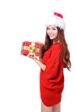 Young happy girl in Christmas hat holding gift. Young happy girl in Christmas hat holding huge christmas gift isolated on white background Royalty Free Stock Images