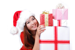 Young happy girl in Christmas hat holding gift. Young happy girl in Christmas hat smile holding huge christmas gift isolated on white background Stock Photos