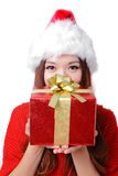 Young happy girl in Christmas hat holding gift. Young happy girl in Christmas hat holding huge christmas gift isolated on white background Stock Images