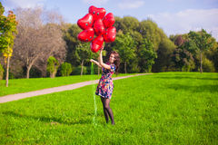 Young happy girl in colorful dress have fun with red balloons outside Royalty Free Stock Photo