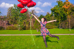 Young happy girl in colorful dress have fun with red balloons outside Royalty Free Stock Photography