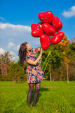 Young happy girl in colorful dress have fun with red balloons outside Stock Image