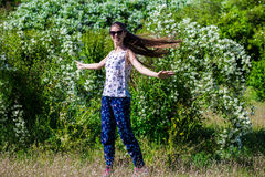 Young happy girl is dancing in the park stock image