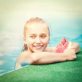 Young happy girl eating watermelon in pool Stock Photo