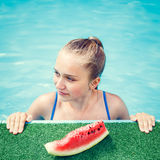 Young happy girl eating watermelon in pool Royalty Free Stock Photo
