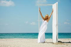 Young happy girl entering door on sea background Royalty Free Stock Photos