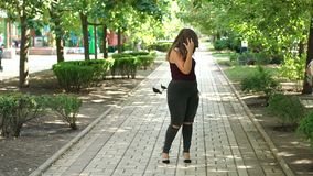 A young happy girl with excess weight walks in a summer park. Plus size model. A young happy girl with excess weight walks in a summer park, she swims around stock video