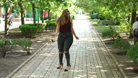 Portrait of an overweight girl in Park in summer. A young happy girl with excess weight walks in a summer park, she swims around herself and enjoys warm weather stock footage