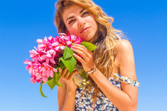 Young happy girl with flower bouquet on tropical sea and beach b Stock Images