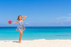 Young happy girl with flower bouquet on tropical sea and beach b Stock Photos