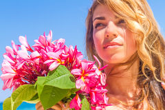 Young happy girl with flower bouquet on tropical sea and beach b Stock Photography