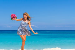 Young happy girl with flower bouquet on tropical sea and beach b Stock Image
