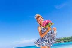 Young happy girl with flower bouquet on tropical sea and beach Royalty Free Stock Image