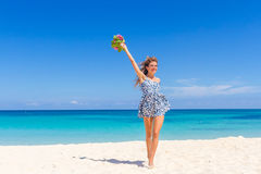 Young happy girl with flower bouquet on tropical sea and beach Royalty Free Stock Images