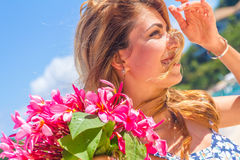 Young happy girl with flower bouquet on tropical sea and beach Stock Photo