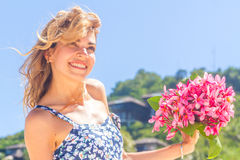 Young happy girl with flower bouquet on tropical sea and beach Stock Image
