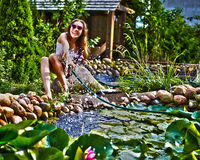 Young happy girl with garden streamlet near pond Stock Images