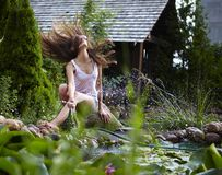 Young happy girl with garden streamlet near pond Royalty Free Stock Images