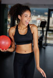 Young happy girl gives a cute smile to you while working out at gym Royalty Free Stock Photos