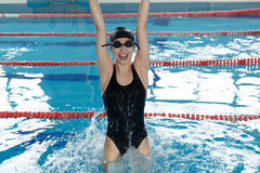 Young happy girl in goggles and cap jumping in the swimming pool. Stock Photos