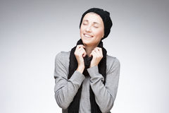 Young happy girl on gray background. Studio portrait of young attractive caucasian girl in winter clothing which happy smiling with closed eyes on gradient gray Stock Image