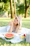 Young happy girl in hat with croissant lying in park on plaid near waterlemon. royalty free stock photo