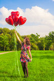 Young happy girl have fun with red balloons outdoor Royalty Free Stock Image