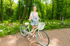 Young happy girl with her bicycle standing on bricks in a park Stock Photography
