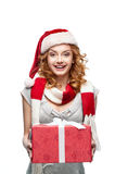 Young happy girl holding christmas gift. Young red-haired european happy smiling girl in santa hat and red and white scarf holding christmas gift Royalty Free Stock Images