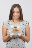 Young happy girl holding a fish tank with goldfish Stock Image