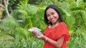 Young happy girl holding in her hands indonesian money. The concept of success. Young happy girl holding in her hands indonesian money. The concept of success stock footage