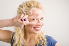 Happy girl holding two fingers in front of her face Royalty Free Stock Image