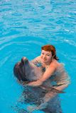 Young happy girl hugs with dolphin. In swimming pool stock photo
