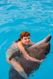 Young happy girl hugs with dolphin. In swimming pool royalty free stock photography