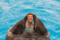 Young happy girl hugs with dolphin. In swimming pool stock images