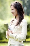 Young and happy girl with laptop. In the park Royalty Free Stock Photos