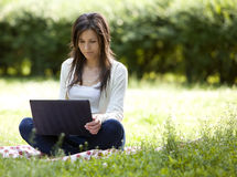 Young and happy girl with laptop. In the park Royalty Free Stock Images