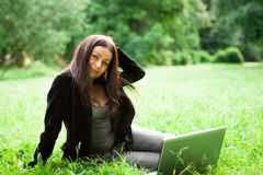 Young and happy girl with laptop. In the park Royalty Free Stock Image