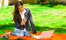 Young and happy girl with laptop in the park using her cellphone Stock Photography