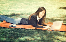 Young and happy girl with laptop in the park, vintage effect.  Royalty Free Stock Images