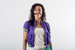 Young happy girl laughing, holding her hair, imitating mustache , wearing trendy outfit. Royalty Free Stock Images