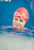 Young happy girl learning to swim in the pool royalty free stock images